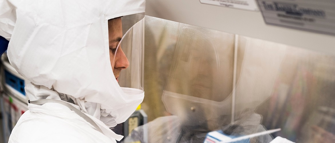Dressed in personal protective equipment (PPE) with an integrated breathing system, a researcher demonstrates proper biosafety practices in the lab for a group of media representatives touring the Influenza Research Institute (IRI) at the University of Wisconsin-Madison on Feb. 28, 2017. The high-security research facility was closed down for annual decontamination, cleaning and maintenance. (Photo by Jeff Miller/UW-Madison)