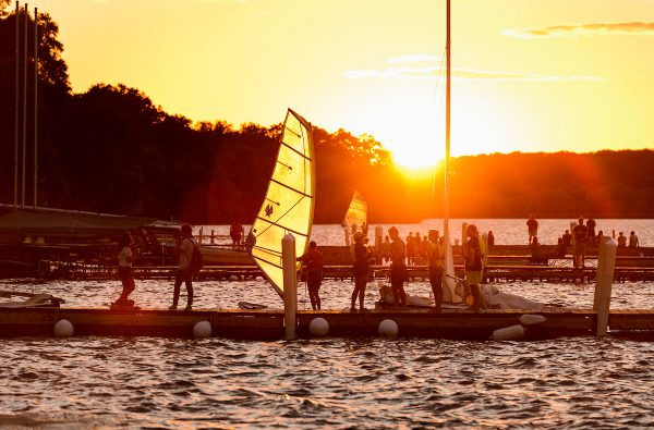 Hoofer Sailing Club members bring their windsurfing boards and sailboats in for the evening near the Memorial Union Terrace at the University of Wisconsin-Madison as the summer sun sets over a Lake Mendota pier on Aug. 31, 2016.