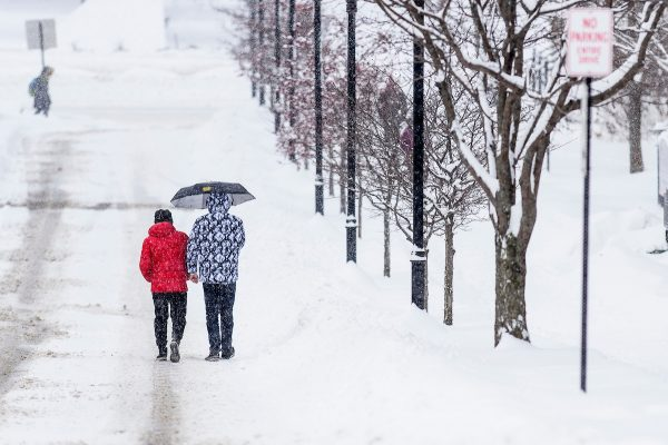 Students and pedestrians walk along snow-covered sidewalks near Agricultural Hall at the University of Wisconsin-Madison during a winter storm that brought several inches of snow to campus on Jan. 23, 2019.