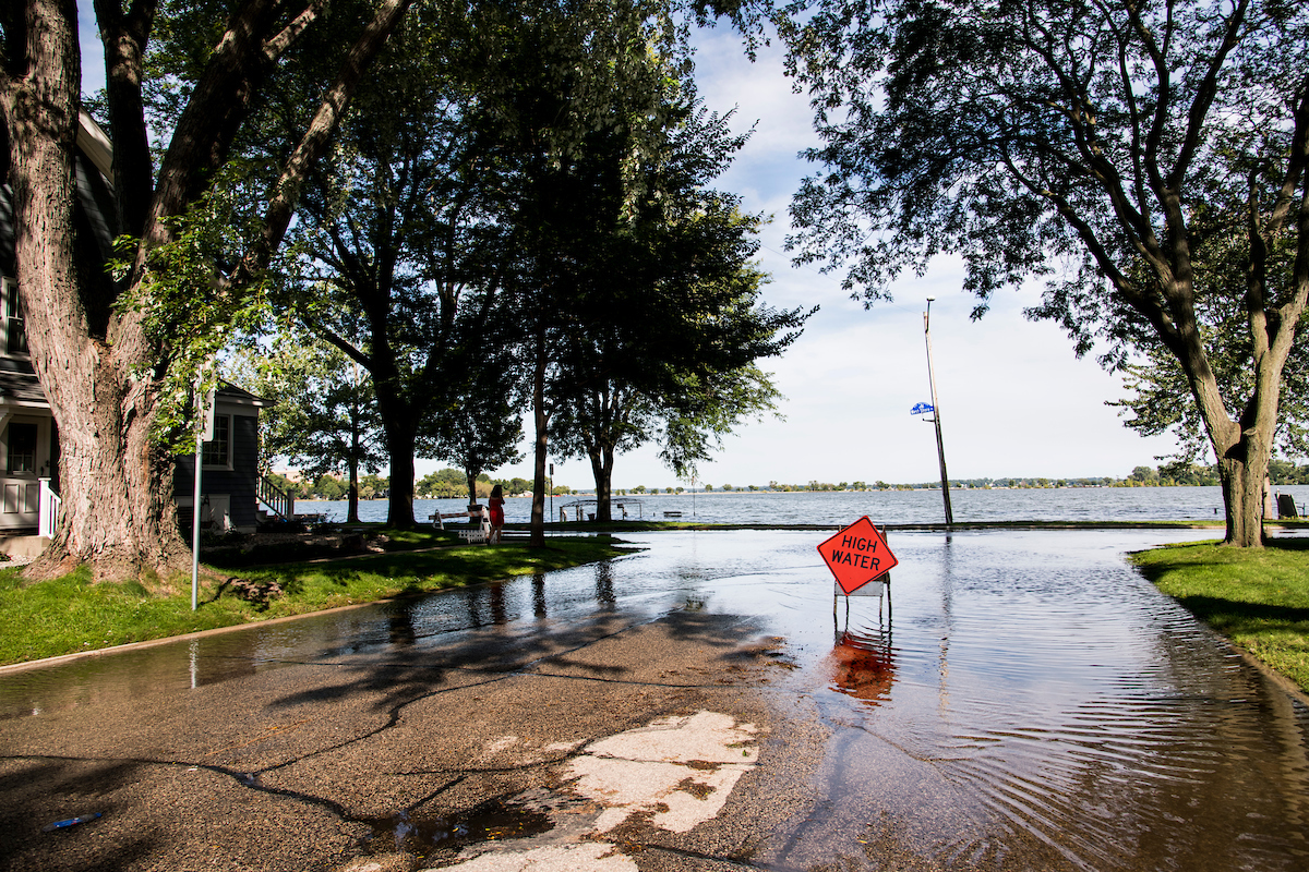A road hazard sign warns of high-standing water flooding West Shore Drive along Monona Bay in Madison, Wis., during summer on Sept. 6, 2018. Area lake levels continue to rise after a record-breaking storm on Aug. 20 dumped more than 10-inches of rain on parts of Dane County, also flooding areas of the University of Wisconsin-Madison campus lakeshore. (Photo by Jeff Miller / UW-Madison)