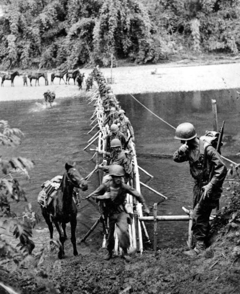 soldiers cross river on bamboo bridge